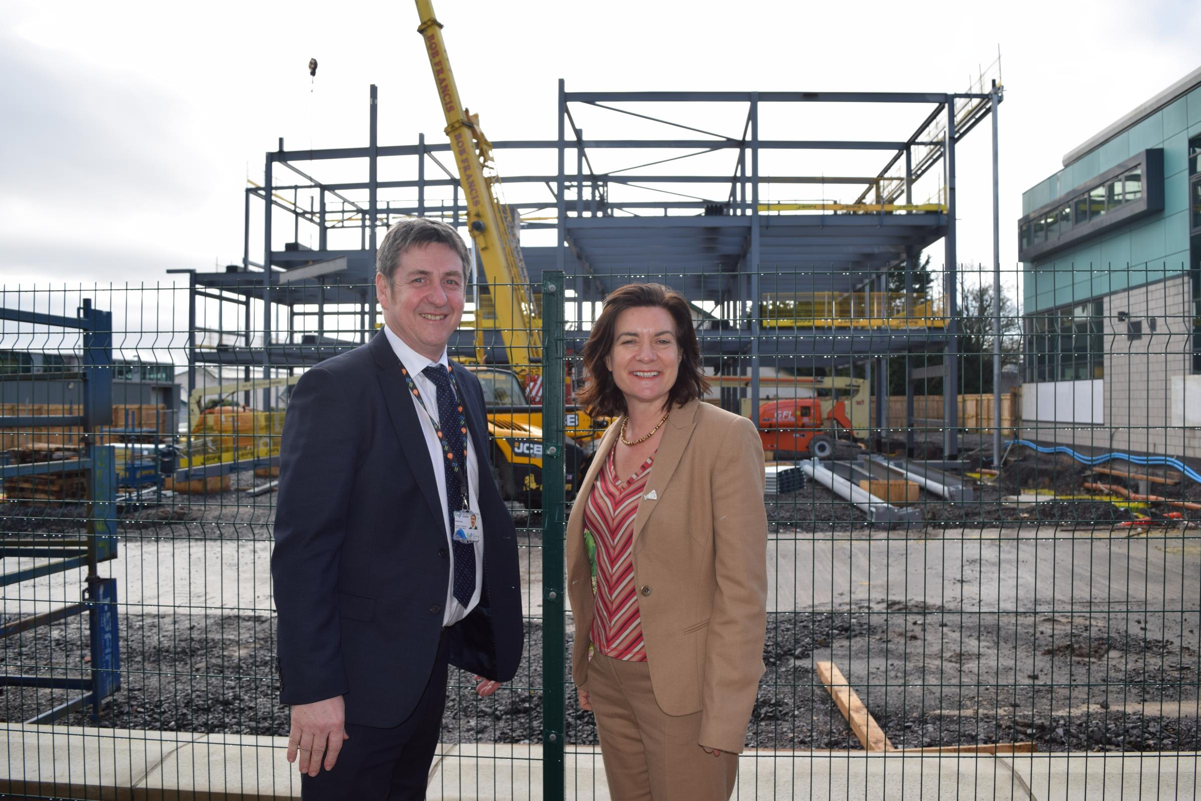 Dafydd Evans and Eluned Morgan against the backdrop of Coleg Menai's new Engineering Centre (currently under construction).