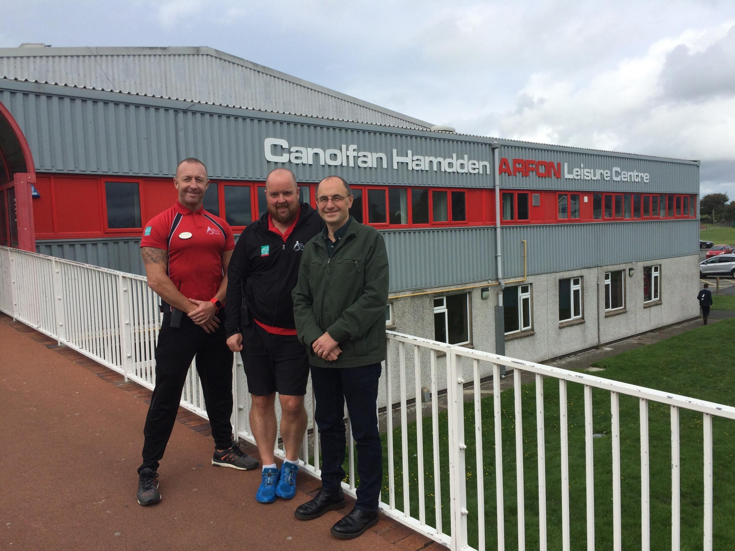 Photograph: Councillor Dafydd Meurig (right), Cabinet Member for the Environment, with Energy Champions Darren Anthony and Neil Owen outside Arfon Leisure Centre