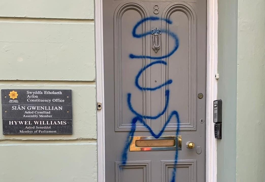 Photograph of Plaid Cymru office in Caernarfon, vandalised with the word 'Scum' on the door